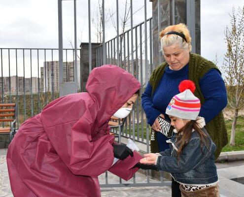 Desinfektion bei einer Hilfspaketverteilung auf dem Gelände von DIACONIA